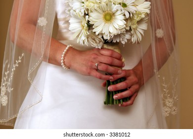 Bride holding a bouquet of flowers in anticipation, displaying her wedding ring