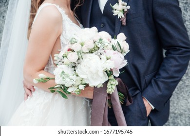 bride holding a bouquet of flowers in her hand, the groom embracing her