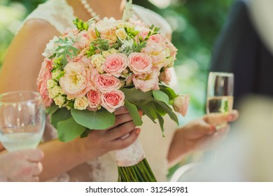 the bride holding a bouquet and glass of champagne