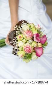 Bride holding a bouquet of purple callas