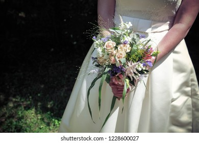A bride holding a bouquet of roses, ribbons and eucalyptus leaves in her hands