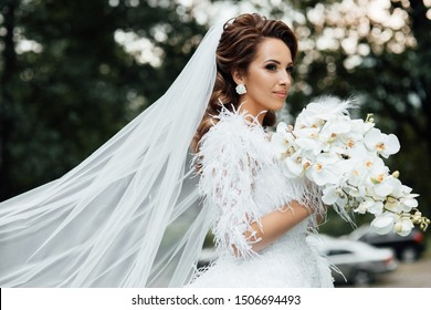 Bride holding a bouquet of white orchids. Beautiful woman. Wedding bouquet in bride's hands. Beautiful bride in white dress in the garden. Beautiful woman with professional make up and hair style.