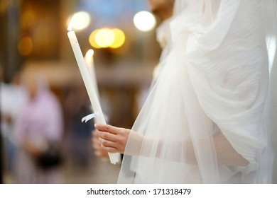 Bride holding candle during an orthodox wedding ceremony