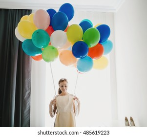 Bride is holding a dress and balloons
