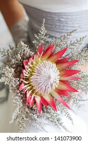 Bride holding her beautiful protea flower wedding bouquet
