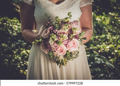 Bride holding her boho wedding bouquet. Perfect image for wedding style magazines and websites, copyspace, fashion, bohemian, flowers decoration businesses, florist and other related subjects.