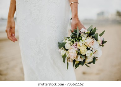 Bride holding her bridal bouquet on the beach