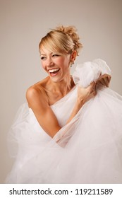 Bride is  holding her dress and laughing
