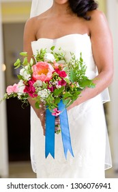 bride holding her wedding bouquet of flowers with blue ribbons and pink and red flowers
