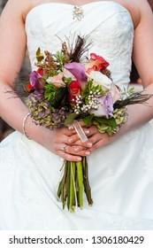 bride holding  her wedding bouquet with purple, red, and white flowers