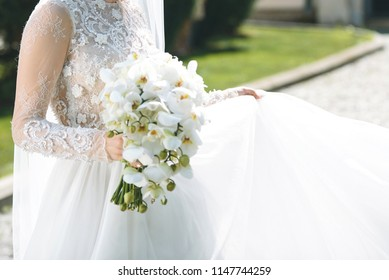 bride holding orchid bouquet and skirt of wedding dress