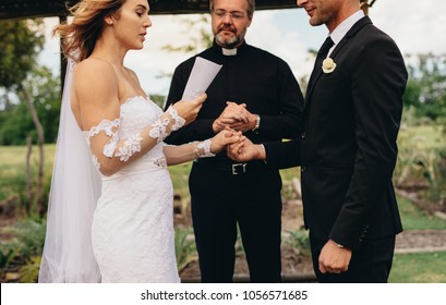 Bride holding a paper and reading wedding vows, with minister standing in the background. Couple exchanging vows on wedding ceremony.