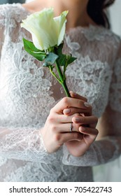 The bride is holding a rose.