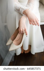 The bride is holding shoes in her hands, wedding shoes, Light shoes in the hands of a girl, White wedding dress, Female hands closeup, wedding day, Stylish image of the bride
