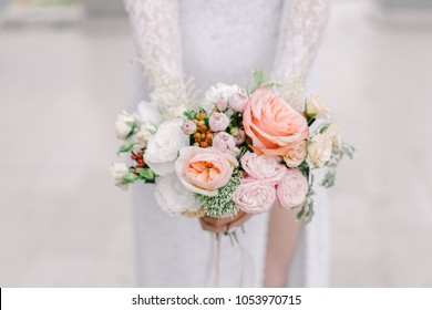 The bride holding soft wedding bouquet of roses, peonies and eustoma, horizontal shot