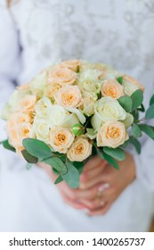 The bride is holding a wedding bouquet. beautiful wedding bouquet of roses. close up.