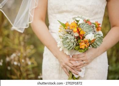 Bride holding wedding bouquet with Echeveria, Dahlia, Freesia, mini Hydrangea, Ranunculus, and Silver Brunia