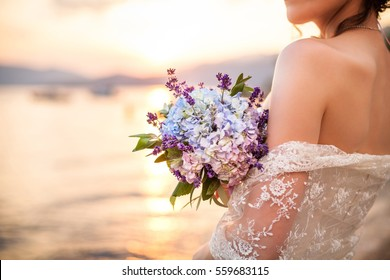 The bride is holding wedding bouquet from lavender and hydrangea and standing on background of the sea and sunset after wedding ceremony.