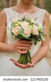 Bride holding a wedding bouquet in pastel pink colors.