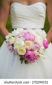 Bride holding wedding bouquet with Peonies, garden Roses, and Sweet pea flowers