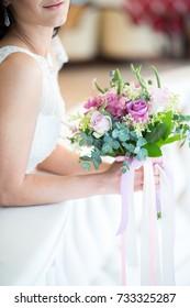 Bride holding wedding bouquet in studio