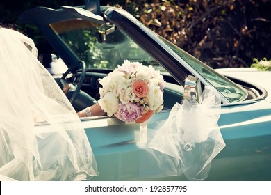 Bride Holding a Wedding Bouquet in an Vintage Car