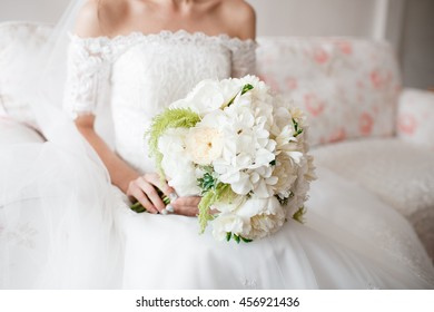 Bride holding wedding bouquet of white Garden rose peony