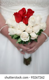 Bride holding wedding flower bouquet of red and white roses