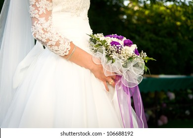 Bride holding wedding flowers.