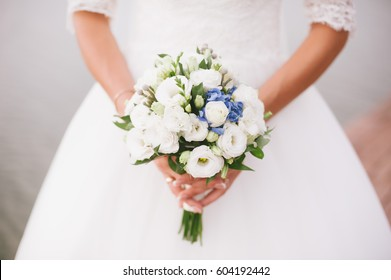 The bride holds a beautiful bouquet of flowers on a background of lake