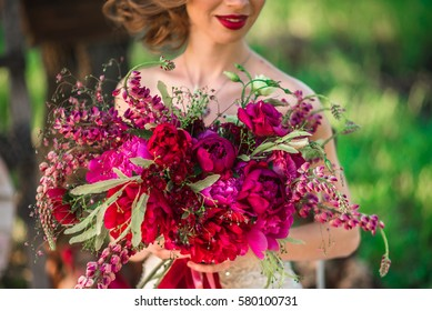 The bride holds a chic wedding bouquet of roses and peony.