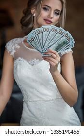 A bride holds dollars fan in loft interior room