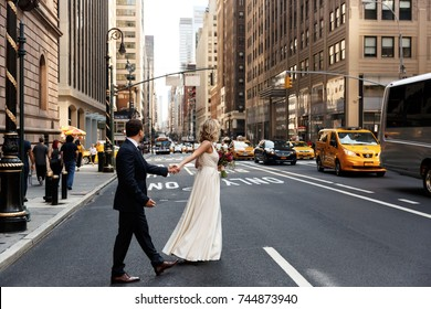 Bride holds groom's hand walking across the street in New York