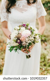 Bride holds in hands a rustic wedding bouquet with white dahlias, peonies, and greens. Artwork. Close-up