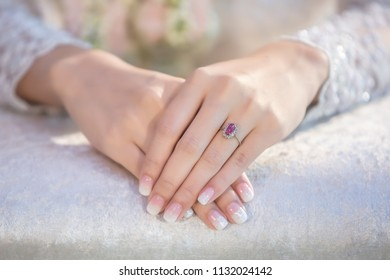 Bride holds her hand on a white beautiful bridal dress and shows her engagement ring.hand and ring on bridal dress of the bride.