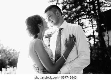 Bride holds her hands on groom's chest while they stand outside