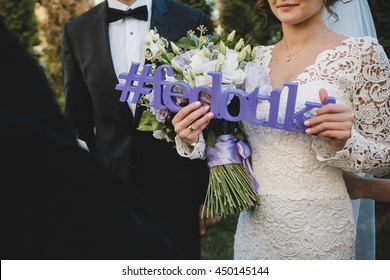 Bride holds in her hands a violet letteing with wedding hashtag