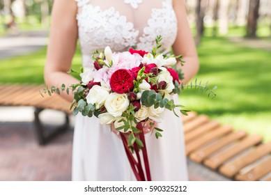 Bride holds in her hands wedding bouquet