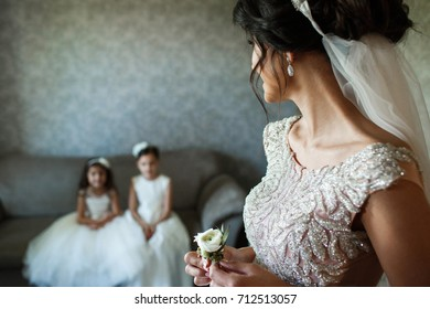 Bride holds little white boutonniere in her arms and looks at little girls