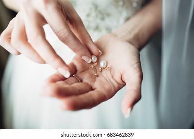 Bride holds pearl earring in her fingers