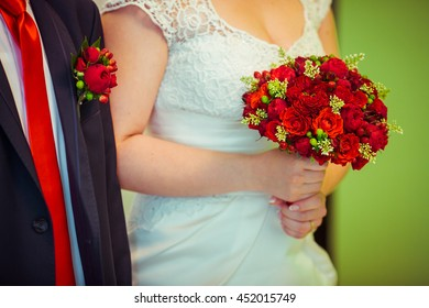 Bride holds red wedding bouquet standing behind a groom in red tie