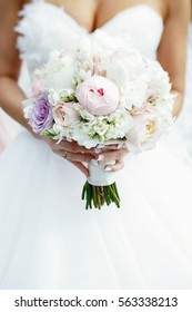 Bride holds tender wedding bouquet made of white and pink peonies