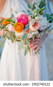 Bride holds wedding bouquet with beautiful flowers and pink silk ribbons