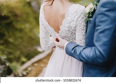 Bride holds a wedding bouquet. Wedding dress, wedding details. Groom hugs bride