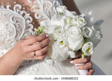 The bride holds a wedding bouquet in her hand against the background of a white dress. Bridal bouquet on the wedding day. Flowers for the bride. A small bridal bouquet close-up.