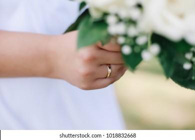 Bride holds a wedding bouquet, wedding ring, wedding details
