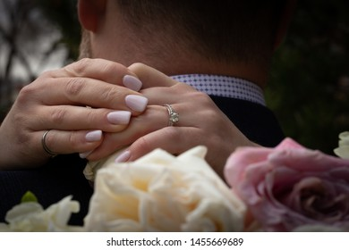 Bride hugging groom around neck with close up of her hands and ring on the back of his suit with bouquet in foreground