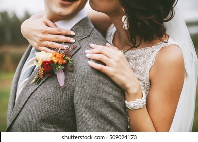 Bride hugging a groom and the details of their outfit: bracelet and a buttonhole
