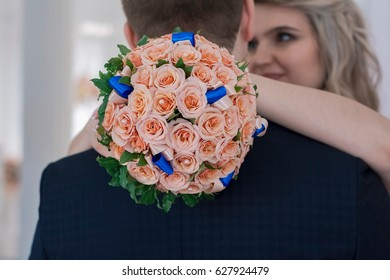 Bride hugging the groom and holding a bouquet of the bride