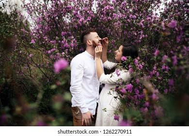 Bride hugs groom tender standing in the blooming park